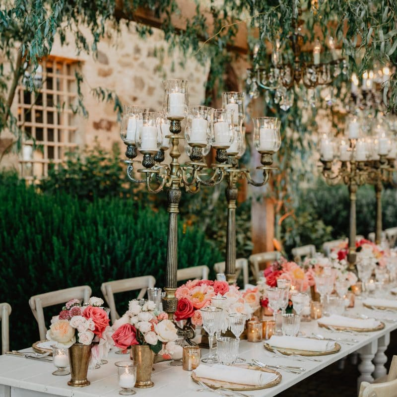Rectangular table with bronze chandeliers and coral and ivory flowers