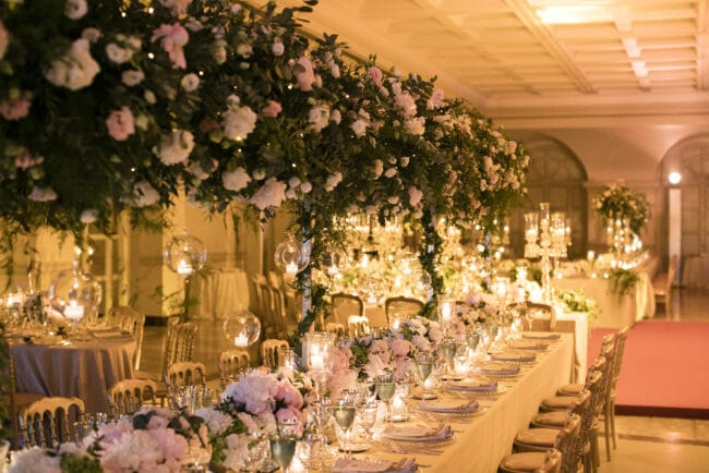 Luxury wedding with rectangular tables with hanging greenery and candles