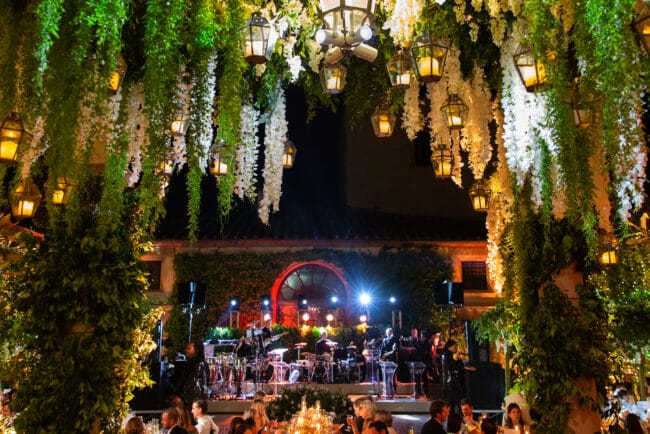 Exclusive wedding party in a villa in Italy with live show band and hanging greenery and lanterns