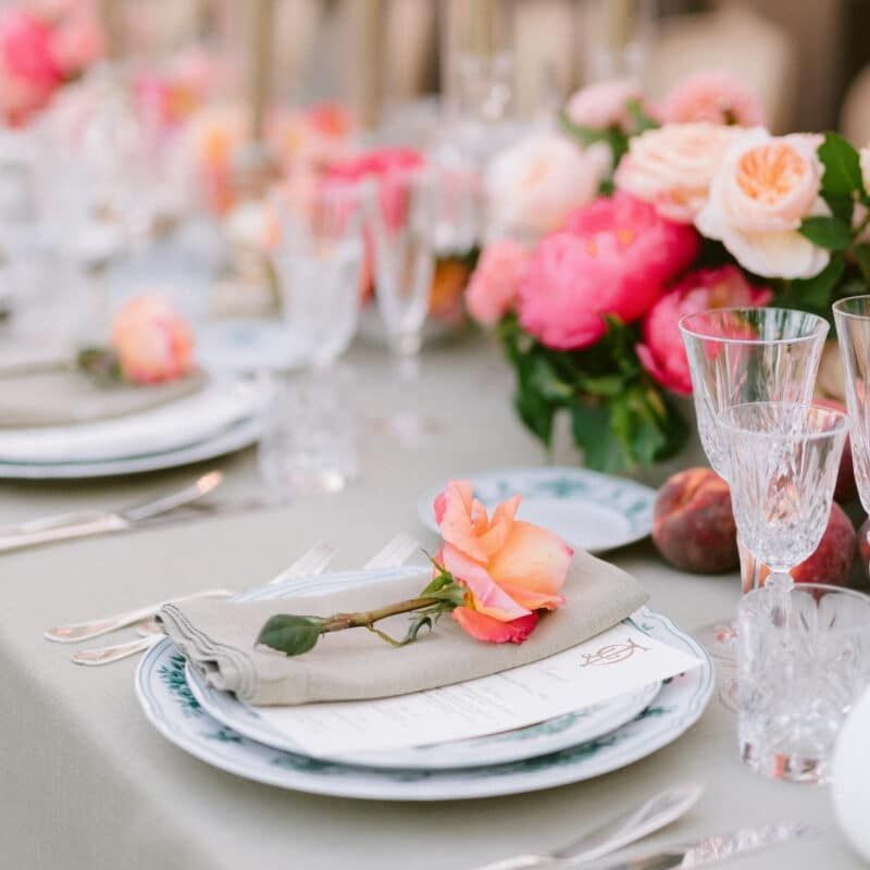 Table setting with sage color tableclothes and orange and pink flowers
