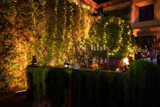 Bar station with greenery and fairlights for a secret garden style wedding in Italy