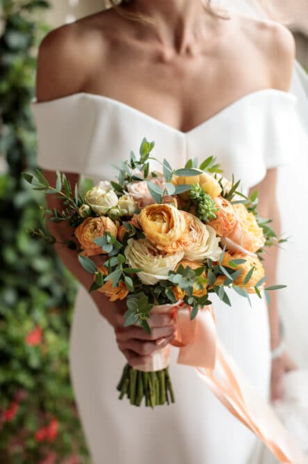 Bride wedding dress with orange bouquet
