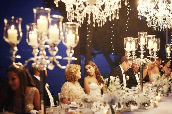 Bride and mother of the bride in the frame of hanging chandeliers and candelabras