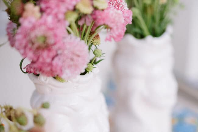 White ceramics vases and pink flowers