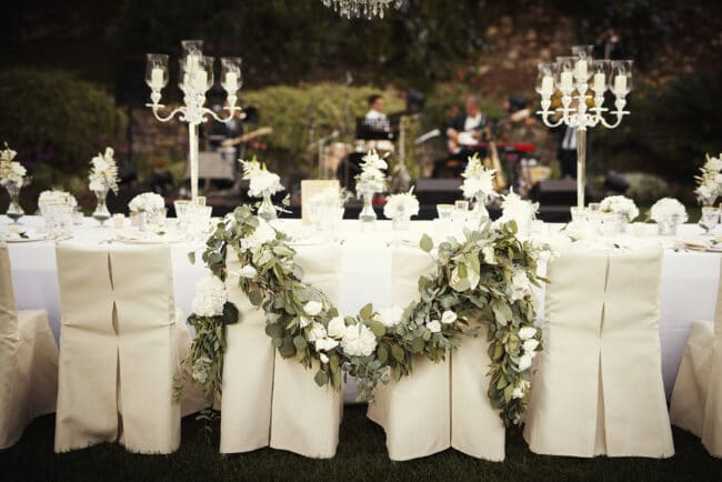 Bride and groom chairs decorated with a garland made with greenery and white flowers