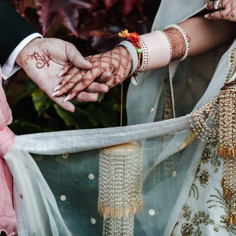 Indian bride and groom hand in hand