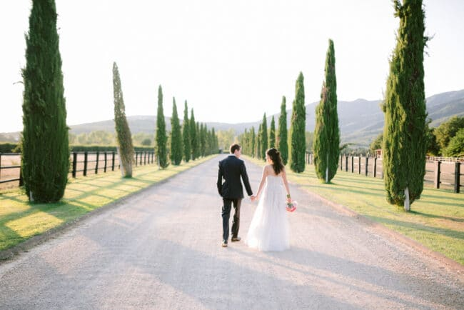 Romantic portrait of the newlyweds holding hands in a Tuscan villa