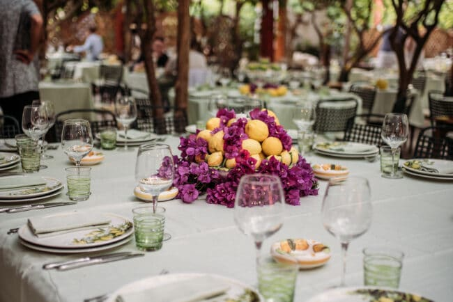 Table decor with fuxia flowers and lemons for welcome wedding dinner in Capri
