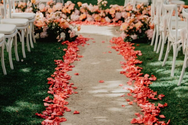 Wedding aisle with coral color petals and ivory carpet