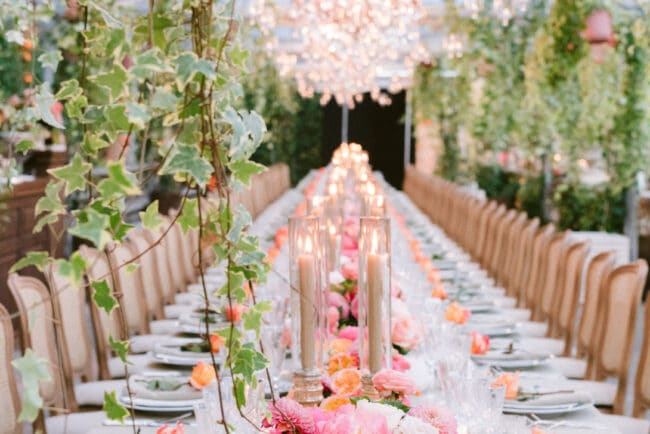 Rectangular table and hanging chandeliers and greenery