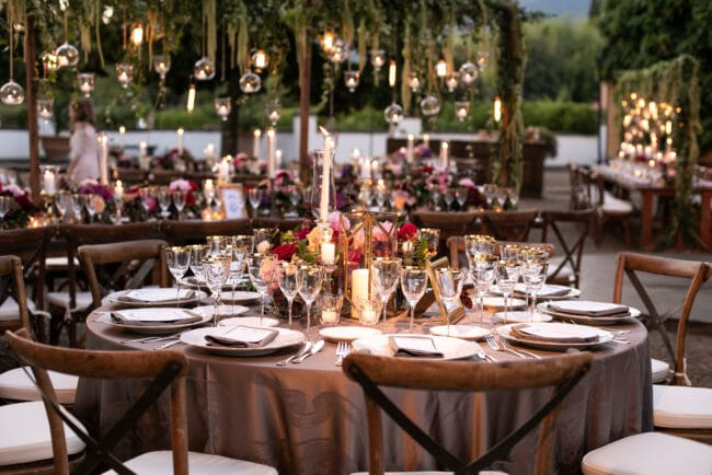 Wedding round table with grey tableclothes and wooden chairs