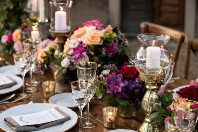 Elegant wedding table decoration with gold candleholders and flowers