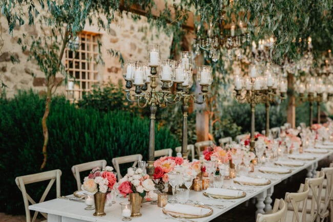 White wooden table and bronze candelabras as wedding decor