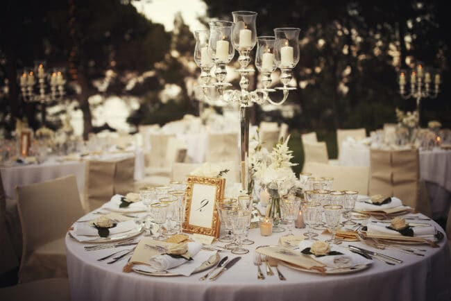 Round wedding table with silver candelabra and white flowers with greenery