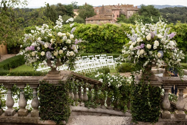 Flowers vases with greenery and white flowers to decor a wedding ceremony