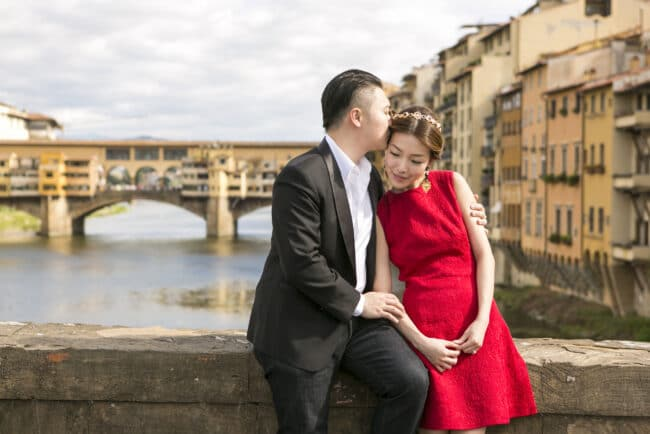 Bride and groom embrace in front of Ponte Vecchio, Florence
