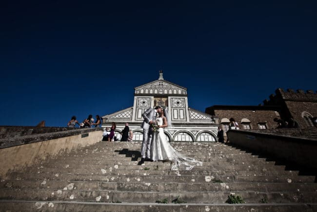 The newlyweds in front of the church kiss during their elopement in Florence