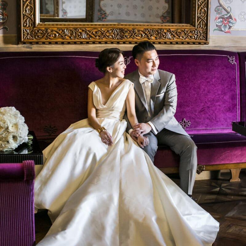 Romantic wedding couple sitting on a purple sofa