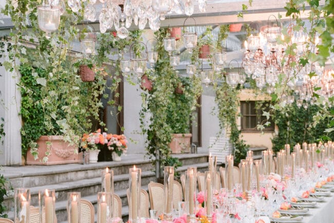 Amazing wedding decor with chandeliers, hanging greenery and peach and coral palette flowers