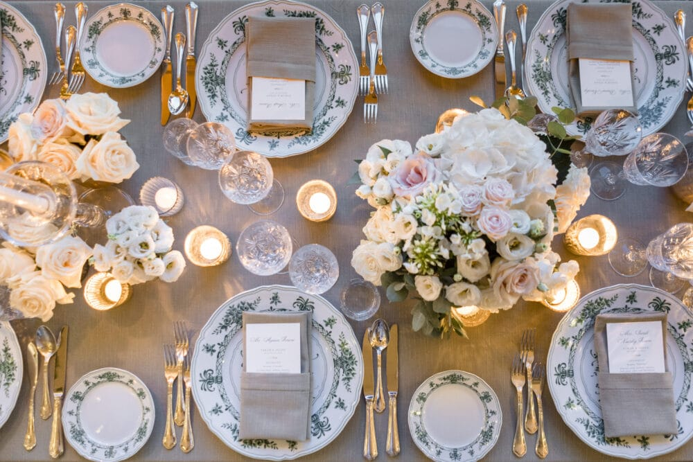 Table setting with ivory and pale rose flowers and green decorated plates