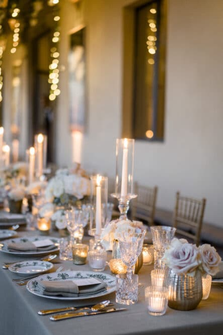 Table setting with sage green color tableclothes, candles and hanging fairylights