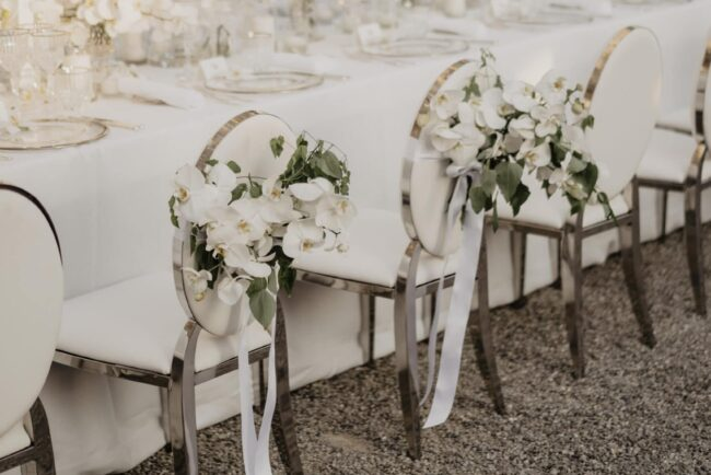 Bride and groom chairs decorated with flowers