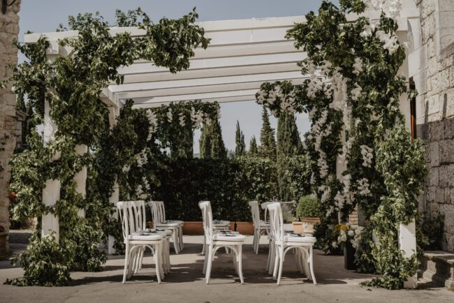 Outside pergola with greenery and white chairs