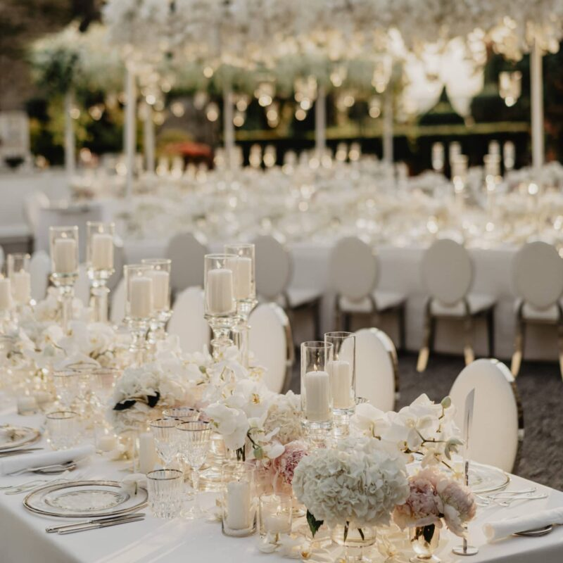 Wedding white tables at the sunset with cascading orchids